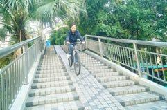 Los hombres chinos montan las bicicletas abajo del puente peatonal Fotos de archivo libres de regalías