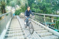 Los hombres chinos montan las bicicletas abajo del puente peatonal Imagen de archivo