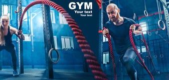 Los hombres con la cuerda de la batalla luchan cuerdas ejercitan en el gimnasio de la aptitud imágenes de archivo libres de regalías
