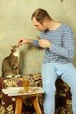 Los hombres con una cerveza al lado del gato roban pescados Foto de archivo libre de regalías