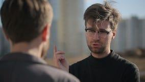Los hombres continúan un diálogo sobre un negocio Cámara lenta almacen de metraje de vídeo