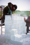 Los hombres cortaron la pared eléctrica del hielo de la sierra en la ciudad de la nieve foto de archivo