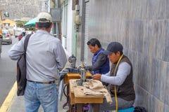 Los hombres cosen en las máquinas de coser en la calle Quito, Ecuador 01/13/2019 imágenes de archivo libres de regalías