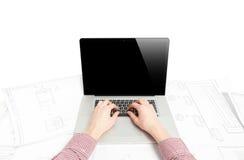 Los hombres dan el trabajo en el ordenador portátil en la tabla con los documentos Imagenes de archivo