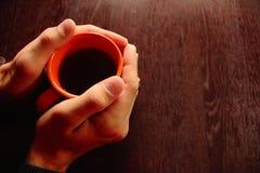 Los hombres dan sostener la taza anaranjada con té negro o café sólo en la tabla de madera marrón como concepto acogedor del desa Imágenes de archivo libres de regalías