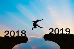 Los hombres de la Feliz Año Nuevo 2019 saltan sobre las montañas de la silueta