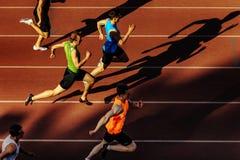 Los hombres de los corredores de la sombra que corren sprint compiten con en el estadio Imagenes de archivo