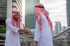 Los hombres de negocios árabes de la sacudida entregan una negociación del trato al éxito imagen de archivo libre de regalías