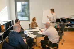 Los hombres de negocios agrupan en la presentación del seminario de la reunión fotografía de archivo libre de regalías