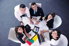 Los hombres de negocios agrupan en una reunión en la oficina Imagen de archivo libre de regalías