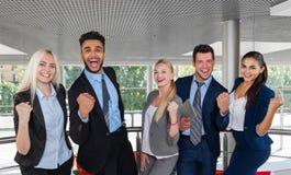 Los hombres de negocios agrupan la sonrisa feliz que se coloca en las manos aumentadas éxito moderno de los empresarios de la ofi Fotos de archivo libres de regalías