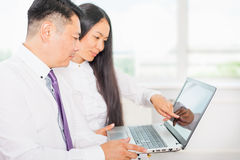 Los hombres de negocios asiáticos analizan el trabajo sobre el ordenador portátil en la oficina Foto de archivo