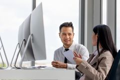 Los hombres de negocios asiáticos jovenes están trabajando juntos en oficina moderna T imagen de archivo