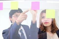 Los hombres de negocios asiáticos jovenes utilizan notas de post-it sobre la pared de cristal para compartir idea en la sala de r imágenes de archivo libres de regalías