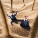 Los hombres de negocios caen en la trampa Imagen de archivo libre de regalías