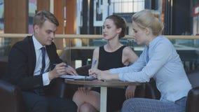 Los hombres de negocios comunican en un café Imagen de archivo