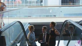 Los hombres de negocios comunican subiendo en la escalera móvil metrajes