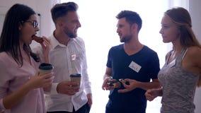 Los hombres de negocios con las insignias comen los bollos con café y la charla juntos en el tiempo de la rotura en oficina metrajes