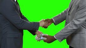 Los hombres de negocios con los dólares sacuden las manos almacen de video