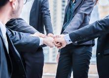 Los hombres de negocios del grupo de manos que hacen que el puño topa trabajo en equipo se unen a concepto acertado de la ayuda d imagen de archivo libre de regalías