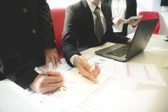 Los hombres de negocios del intercambio de ideas de la reunión de reflexión están escribiendo el plan foto de archivo