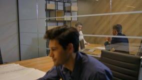 Los hombres de negocios discuten el contrato del trato en la tarde interior de la oficina moderna almacen de video