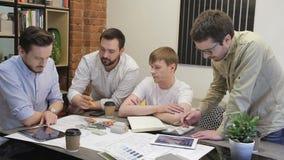 Los hombres de negocios discuten el dibujar de sentarse en la tabla en oficina almacen de video