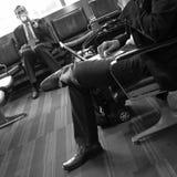 Los hombres de negocios en aeropuerto gandulean para el fllight que espera, vertical Imagen de archivo libre de regalías