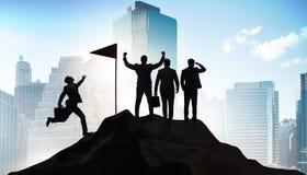 Los hombres de negocios en el logro y el concepto del trabajo en equipo imagenes de archivo