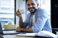 Los hombres de negocios en la camisa azul que se sentaba en oficina con los ordenadores portátiles conectaron con el wifi Imágenes de archivo libres de regalías