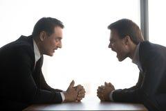 Los hombres de negocios enojados gritan sentarse en la confrontación en la tabla imagenes de archivo