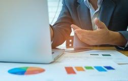 Los hombres de negocios están analizando datos de los gráficos con los ordenadores portátiles y el Ca imagenes de archivo