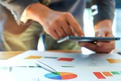 Los hombres de negocios están analizando gráficos y están utilizando las tabletas Foto de archivo