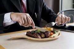 Los hombres de negocios están comiendo el filete Imagen de archivo