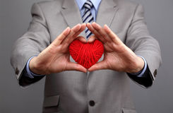 Los hombres de negocios están llevando a cabo hacia fuera un corazón rojo Imagen de archivo