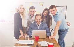 Los hombres de negocios felices combinan juntos cerca del ordenador portátil en oficina Imágenes de archivo libres de regalías