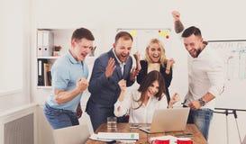 Los hombres de negocios felices del equipo celebran éxito en la oficina Imagen de archivo