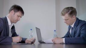 Los hombres de negocios firman e intercambian documentos de la transacci?n entonces sacuden las manos en oficina almacen de metraje de vídeo