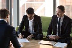 Los hombres de negocios firman el contrato del negocio despu?s de negociaciones acertadas fotografía de archivo libre de regalías