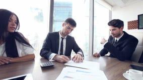 Los hombres de negocios firman el contrato y sacuden las manos