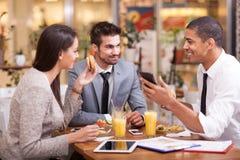 Los hombres de negocios gozan en almuerzo en el restaurante Imagen de archivo libre de regalías