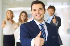 Los hombres de negocios jovenes acertados que muestran los pulgares suben la muestra mientras que se colocan en la oficina más in Foto de archivo