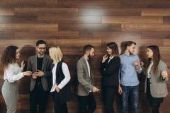 Los hombres de negocios jovenes acertados son que hablan y sonrientes durante el descanso para tomar caf? en oficina fotos de archivo