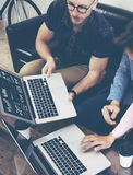 Los hombres de negocios jovenes analizan los artilugios electrónicos modernos del informe de las finanzas del diagrama de la pant imagenes de archivo