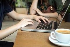 Los hombres de negocios jovenes combinan la elaboración con el ordenador Foto de archivo