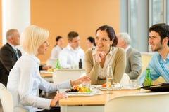 Los hombres de negocios jovenes del almuerzo de la cafetería comen la ensalada