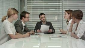 Los hombres de negocios jovenes del grupo tienen reunión en metrajes