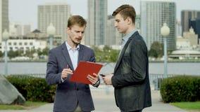 Los hombres de negocios jovenes están discutiendo su negocio en una calle de Coronado, San Diego metrajes