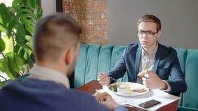 Los hombres de negocios jovenes están hablando durante el almuerzo de negocios, sentándose en la tabla en restaurante almacen de metraje de vídeo