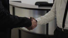 Los hombres de negocios jovenes están sacudiendo las manos que se colocan en el pasillo de la compañía almacen de metraje de vídeo